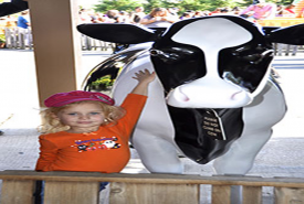 girl standing with fake cow