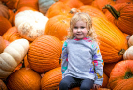 girl happily sitting on pumpkins